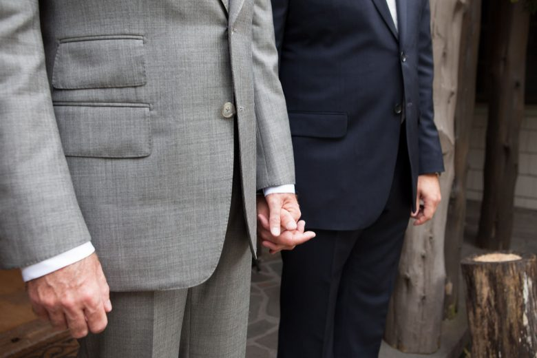 two men holding hands on their wedding day