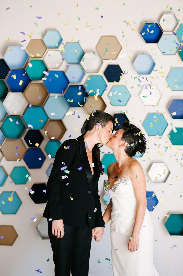 women kissing in front of diy hexagon wedding backdrop