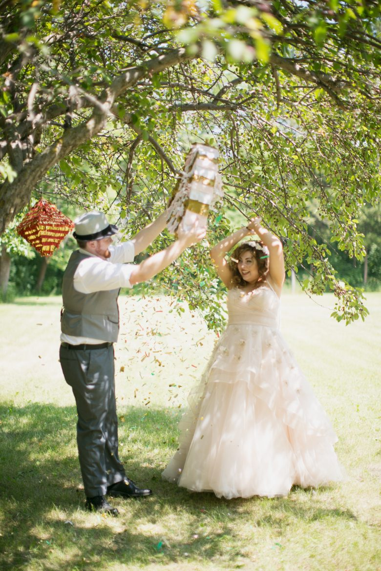 A couple hitting a matrimonial piñata at their backyard wedding