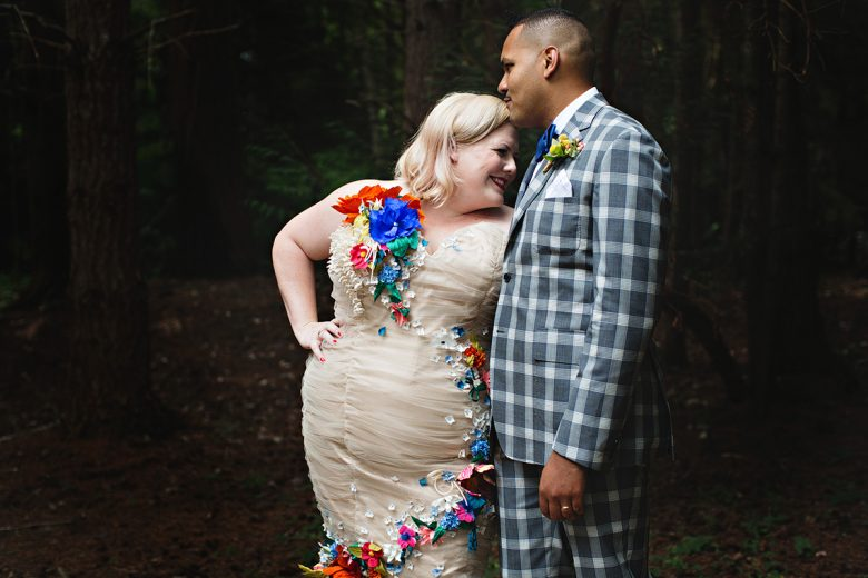 Curly haired man with plaid suit kissing the forehead of a Blonde in dress with fabric flower details | A Practical Wedding