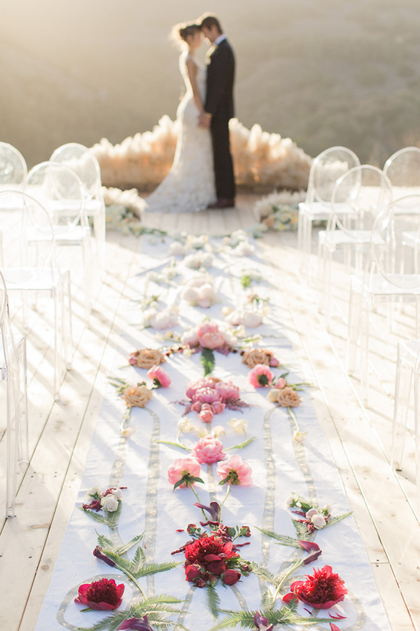 couple standing in front of aisle runner covered in fllowers