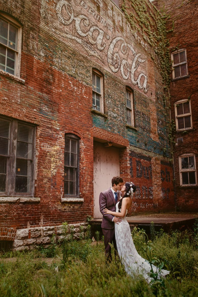 couple standing in front of a brick coca cola sign