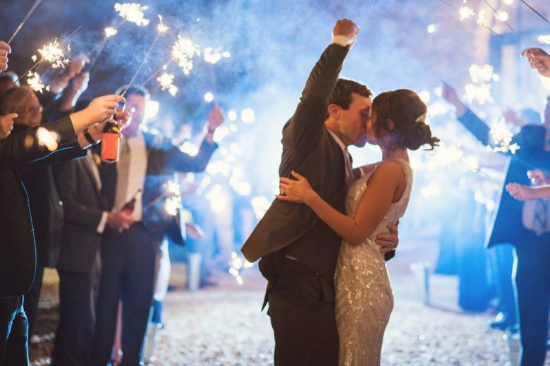 a couple kissing during a sparkler exit