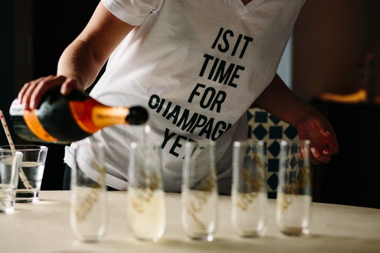 "Woman pouring champagne into glasses, wearing a white t-shirt that reads ""Is it time for champagne yet?"""