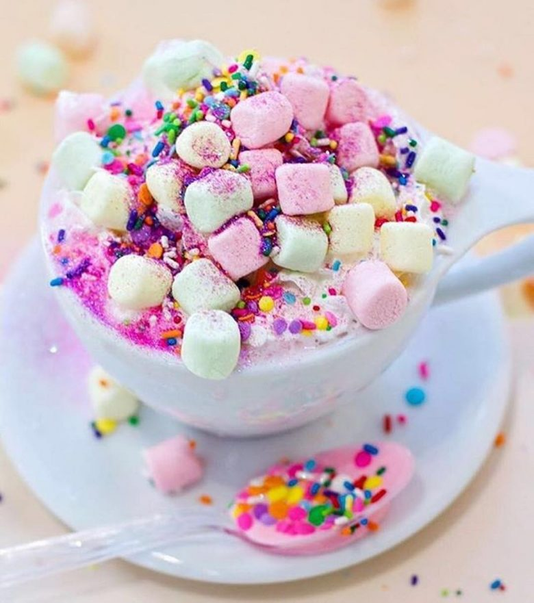 hot chocolate with rainbow sprinkles and pink, yellow, and green marshmallows