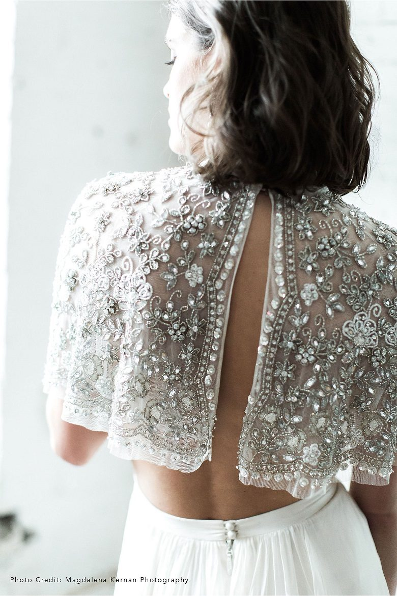 View of a bride's upper back, showing off her half length sparkly cape