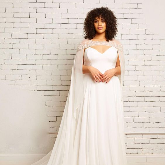 woman in wedding dress and cape with shoulder-length natural curly hair and bangs
