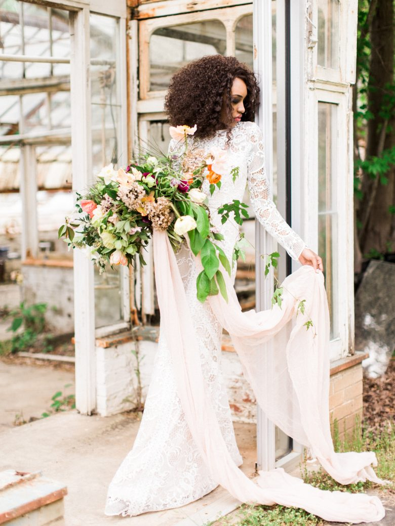 a bride stands elegantly in a doorway holding her bouquet