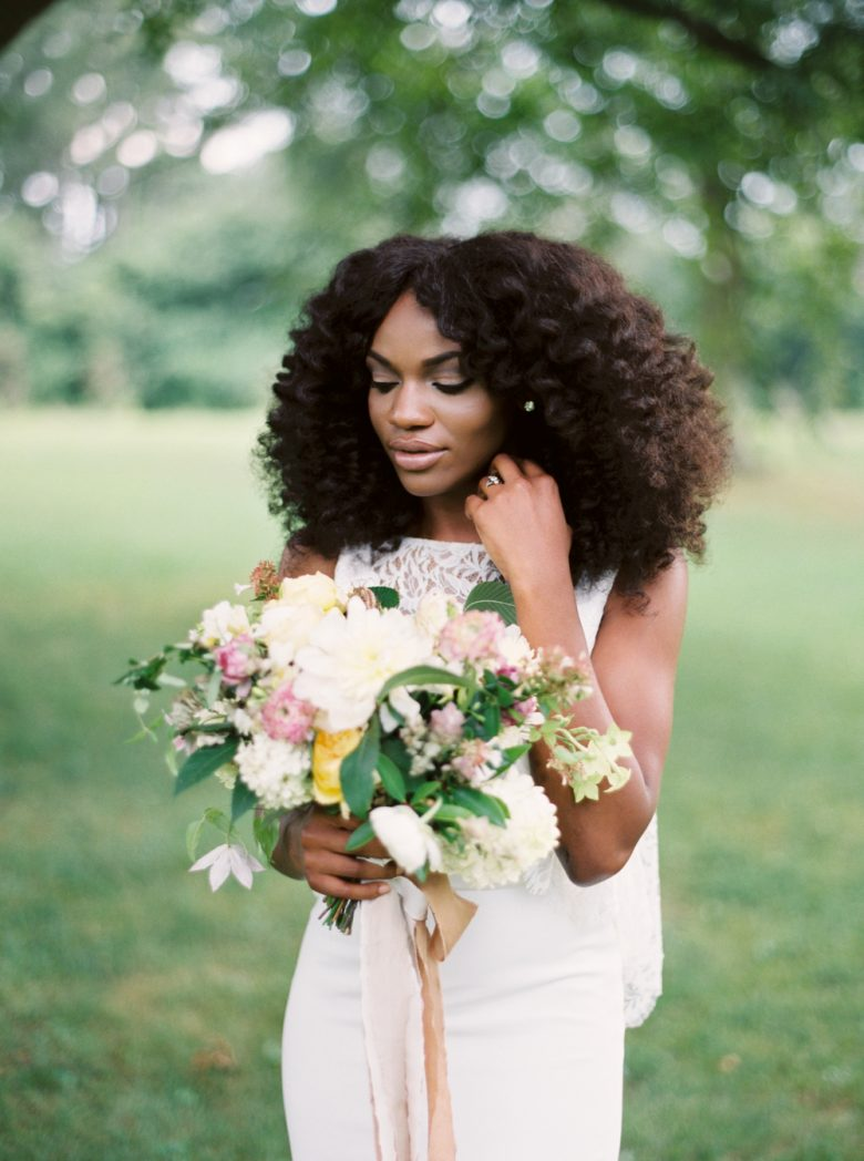 a black woman glances down at her bouquet during bohemian wedding