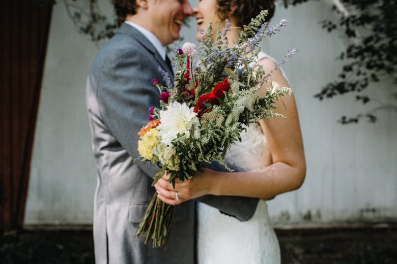 bride and groom laughing while holding bouquet