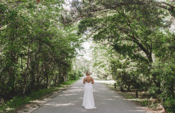 bride standing in a patch of trees