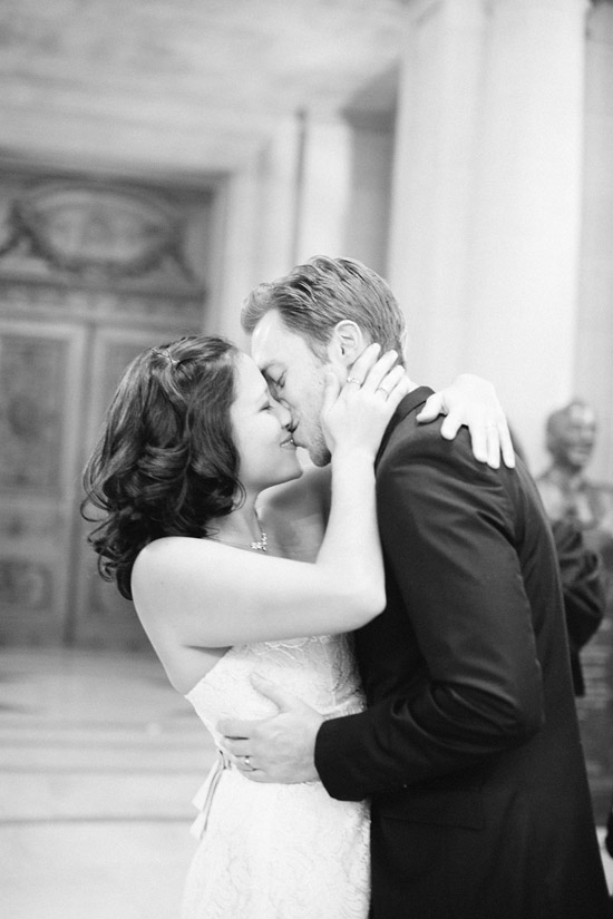 Couple in wedding clothes kissing at San Francisco City Hall