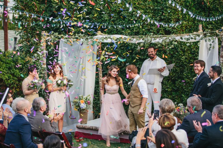 bride and groom leaving their backyard wedding ceremony while confetti cannons go off