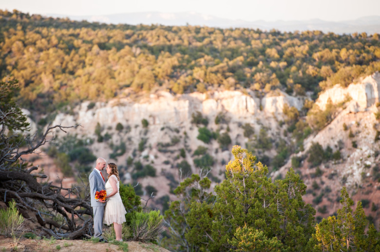 bride and groom standing on a cliff