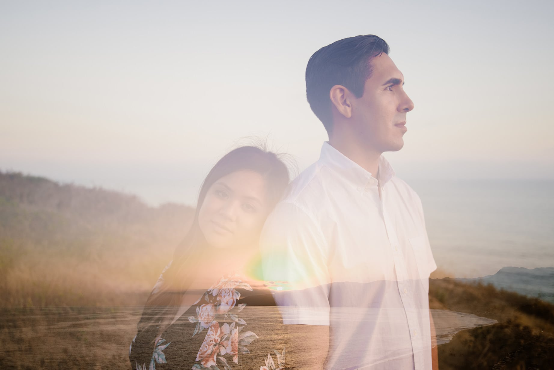 A Julie Pepin photo depicting a double exposed image with a woman leaning on a man as they are back to back. The man looks away and the woman looks at you. The second exposure is of a sunset over water