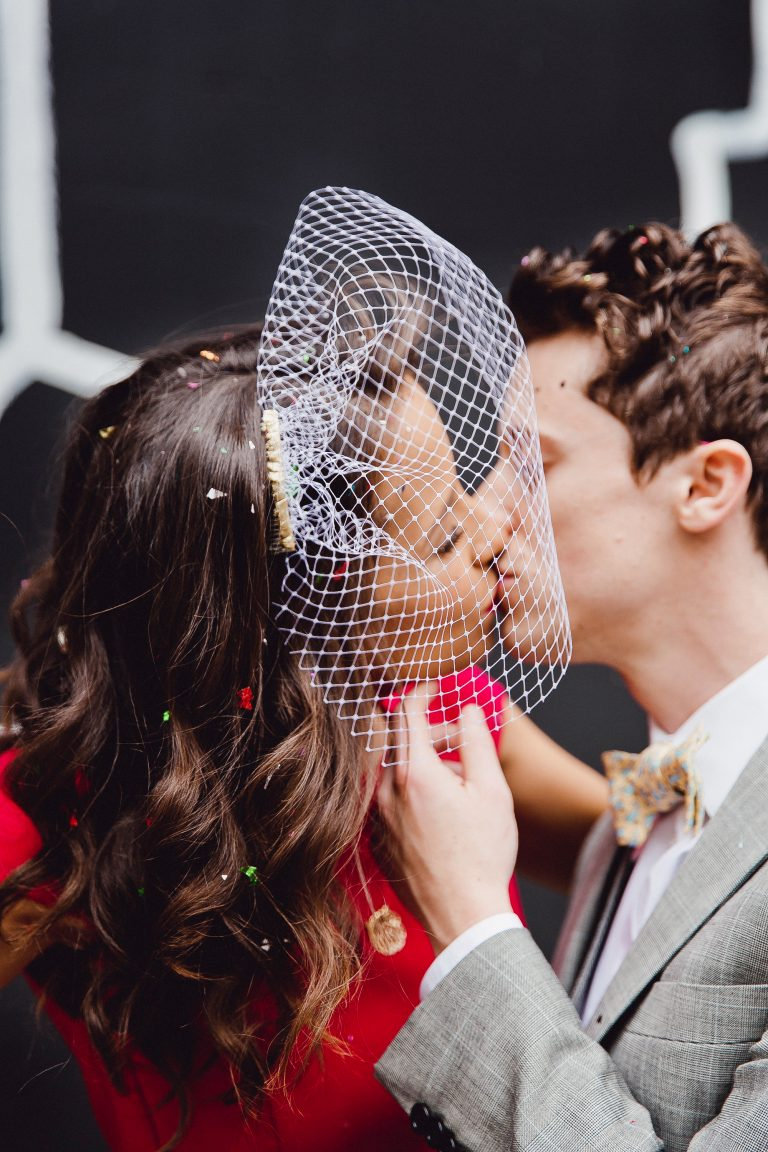 907f4cf3fbcbd Stylish couple kissing with bride wearing a DIY birdcage veil