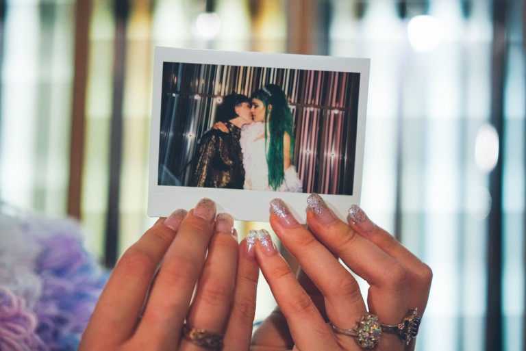 A photo of a pair of hands holding an instant developed photo