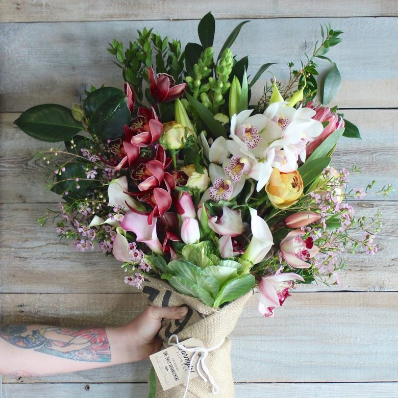 hand holding a bouquet of farmgirl flowers