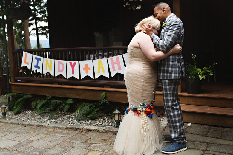 Rainbow letter sign and blonde woman being kissed on the crown of her head by a darker man in plaid | A Practical Wedding