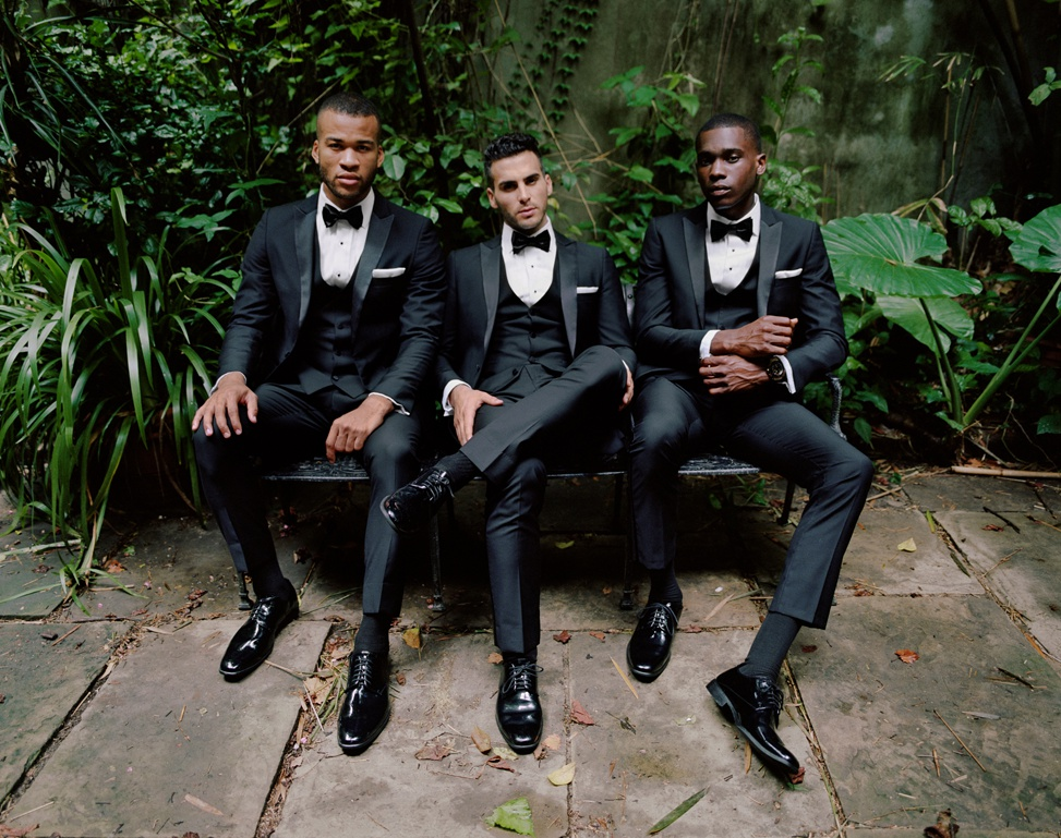 three men sit on a bench wearing black wedding tuxedos for men from generation tux