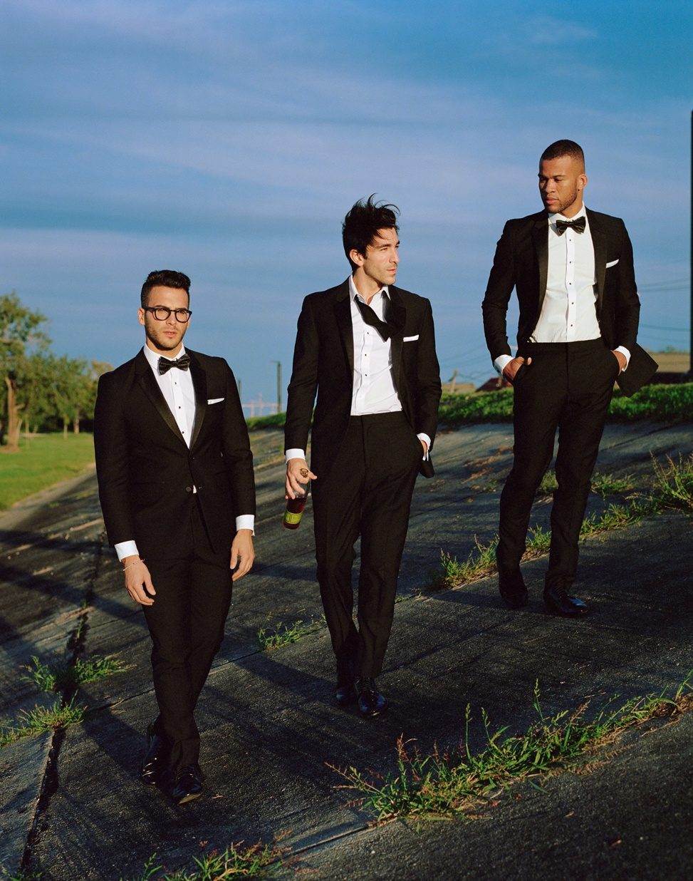Three men walking in generation tux suits. One holds a bottle of alcohol with his bow-tie undone.