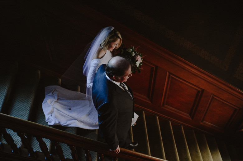 A bride walks down stairs with her father - wedding songs