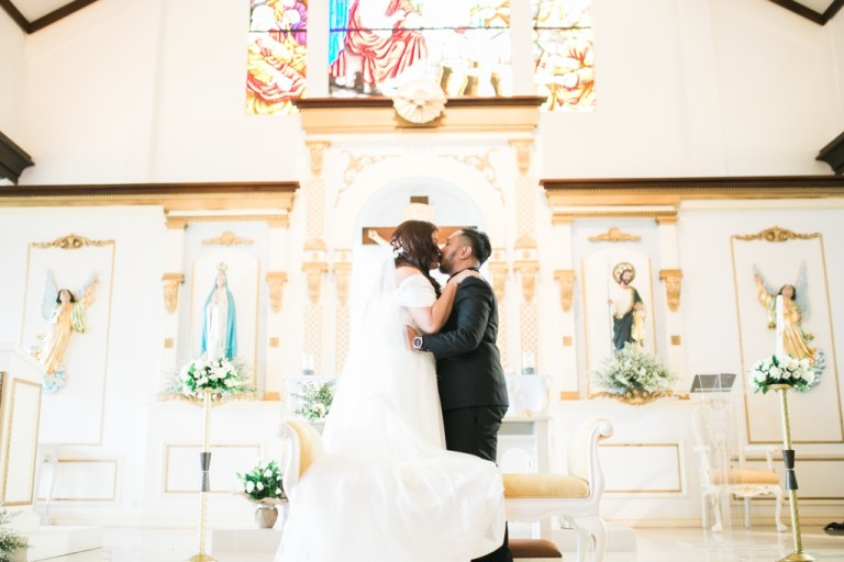 A bride and groom kiss at the altar