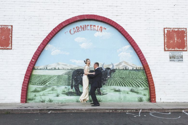 bride and groom jumping in front of a mural