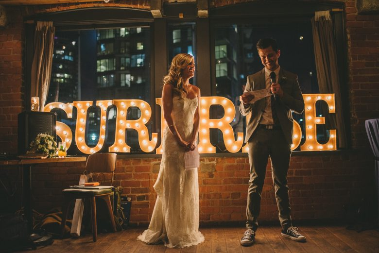 bride and groom speaking in front of surprise sign