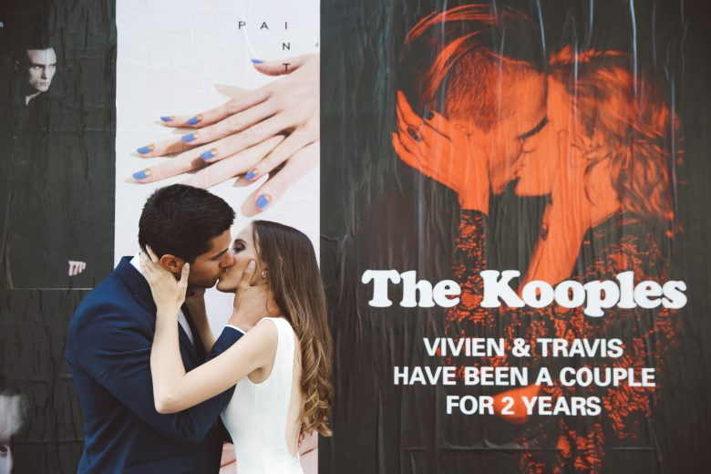 bride and groom kissing in front of sign