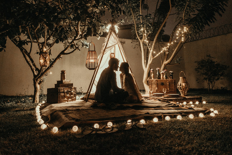 Two persons hanging out with a teepee indicating wedding appropriation