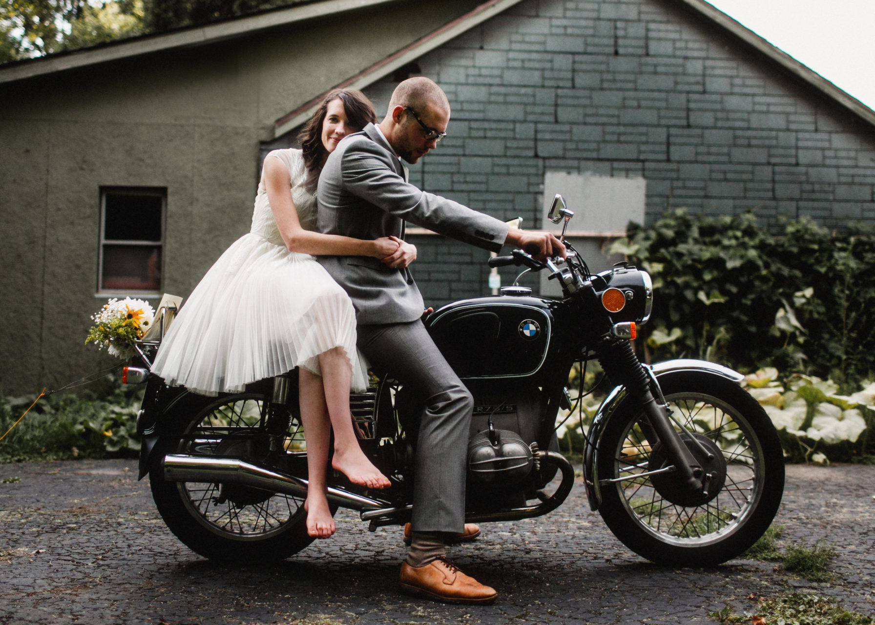 "woman in a wedding dress sitting ""side saddle"" on a motorcycle, hugging a groom sitting on the motorcycle around the waist in a photo by Shaw Photography Co."