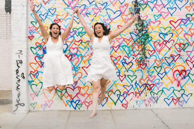 Lesbian couple eloping, jumping in front of a heart wall