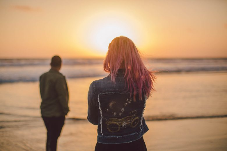 Woman in decorated denim jacket stands with her back to you in the foreground, her partner farther away slightly out of focus, both face the sunset over the ocean