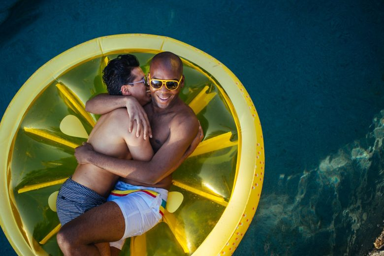 two men snuggling on a pool float