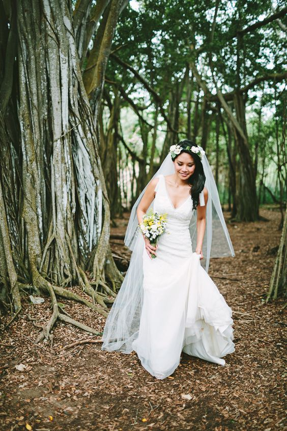 a bride walks through a forrest carrying her wedding dress train in her left hand