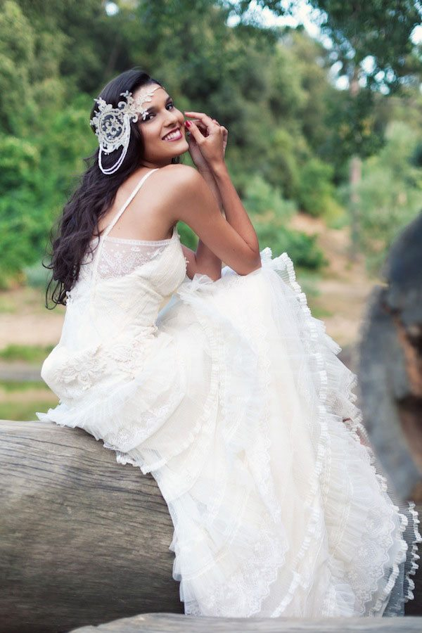 a bride sits casually on a log and looks back over her shoulder and smiles at the camera