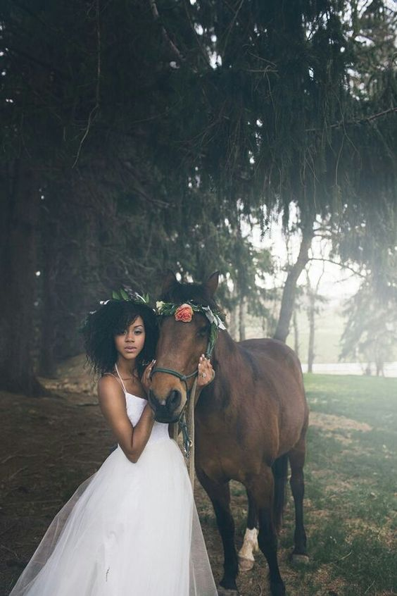 a bride stands beside a horse as the mist rolls in