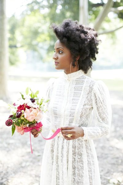 an elegant bride looks off the right as she holds her bouquet