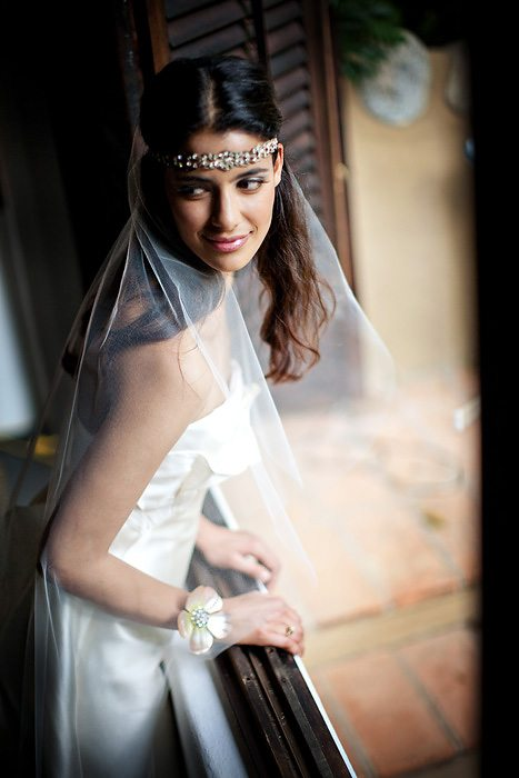 a bride looks mischievously back as she leans at a windows' edge