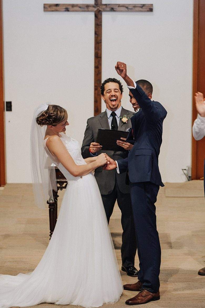Bride, groom, and officiant laughing (groom air-punching)