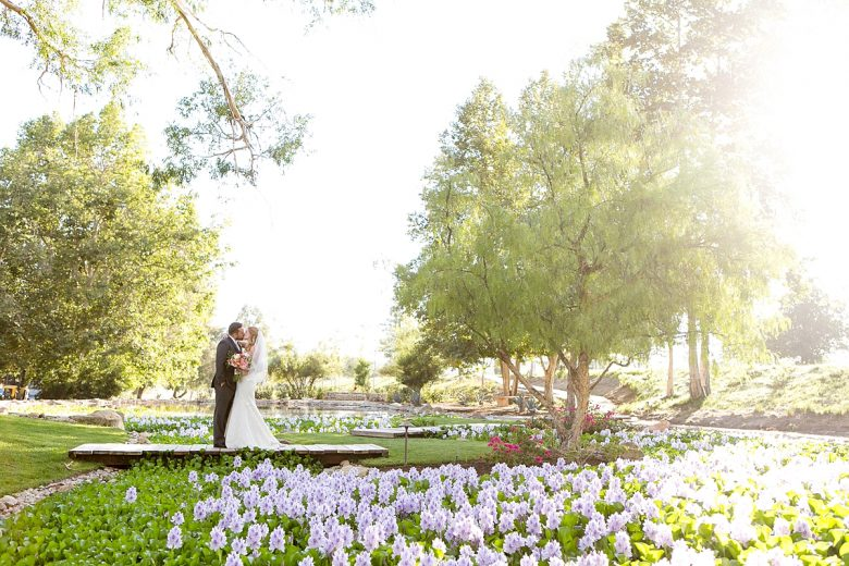 Bride and groom kissing in garden with flowers