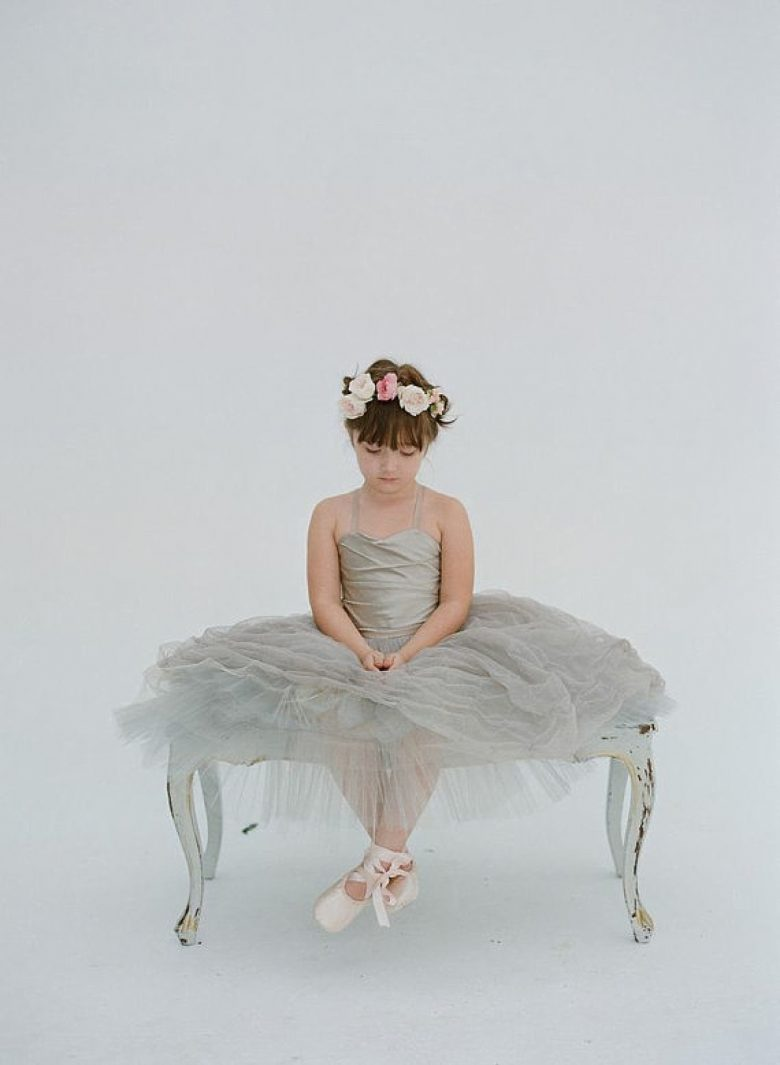 little girl with a flower crown sitting on a bench in a grey tulle dress