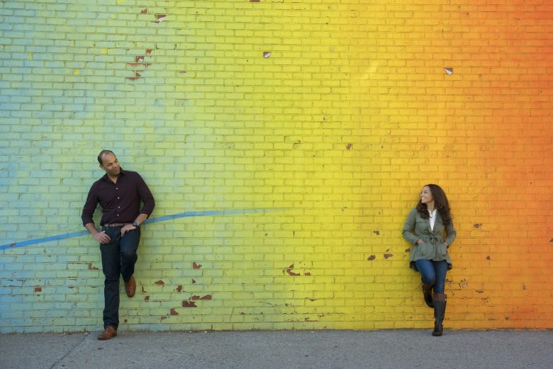 Couple standing in front of ombre blue-green-yellow-orange brick wall