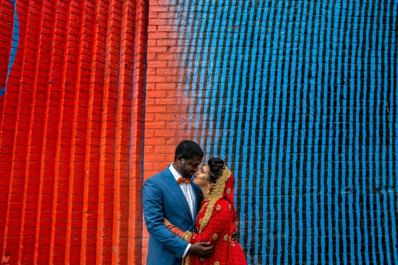 couple wearing blue and red embracing in front of a blue and red graffitied wall