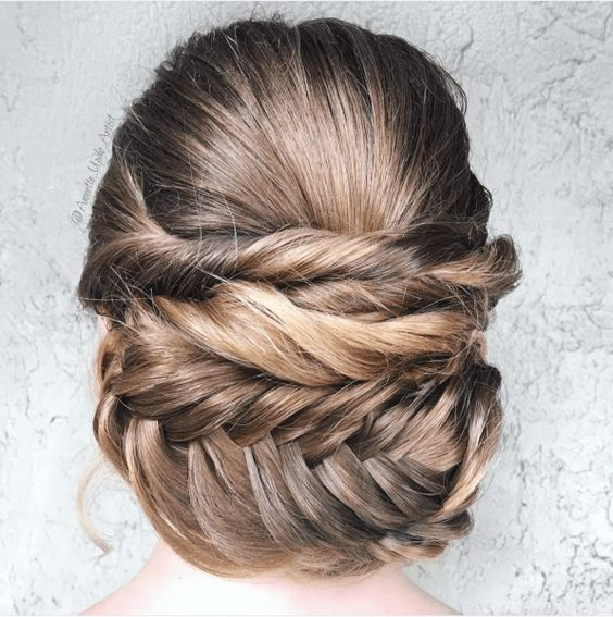 Woman's hair from behind, pulled back into stacked horizontal twists with a thick horizontal fishtail braid for a wedding hairstyle