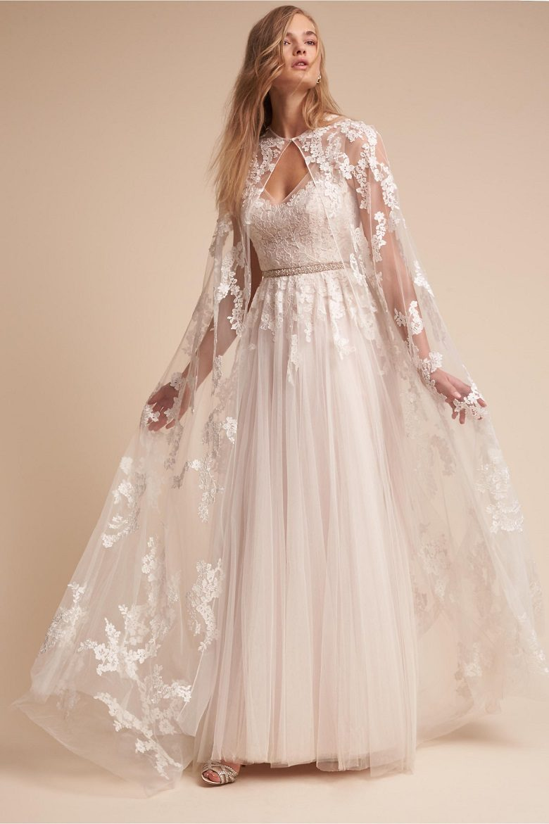 A bride with a lightweight, long wedding dress and a lace full length cape
