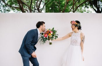 Groom playfully bites at brides bouquet as she laughs