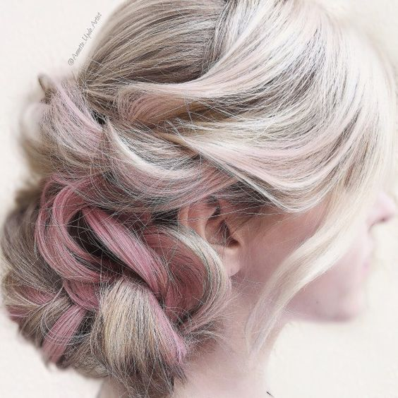 woman with platinum, pink, and dark-streaked hair, piled on the side in a low twisted braid for a wedding hairstyle
