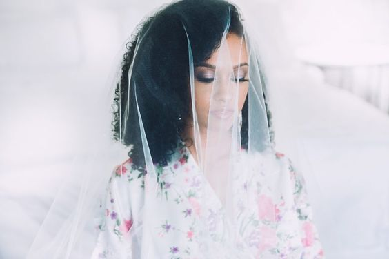 woman covered in veil with shoulder-length natural curly hair for a wedding hairstyle